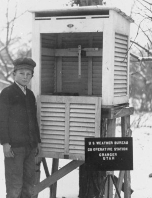 Young child standing next to an instrument shelter.
