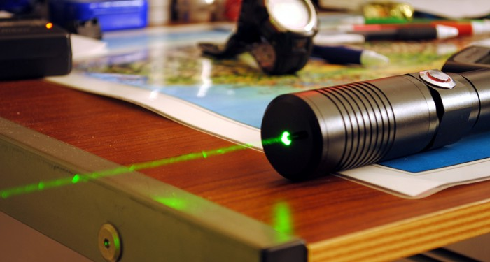 A pocket laser with the beam visible because of dust in the air.